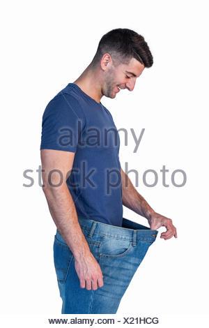 Man smiling alors que l'étirement jeans Banque D'Images