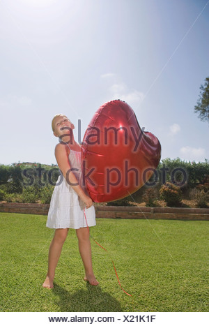 Young Girl holding big red heart balloon Banque D'Images