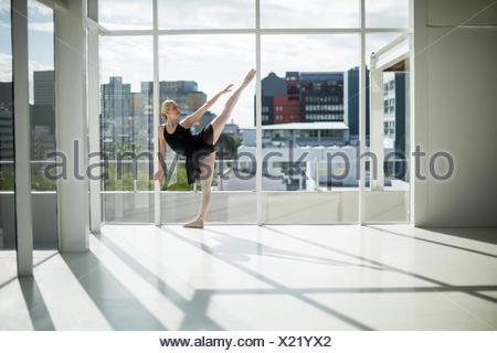 Ballerine qui s'étend sur un mur tout en pratiquant la danse de ballet dans le studio Banque D'Images