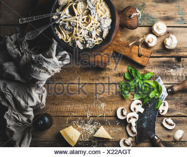 Dîner de style italien avec copie espace. Pâtes aux champignons crémeux spaghettis dans poêle en fonte avec du parmesan, basilic frais et pep Banque D'Images