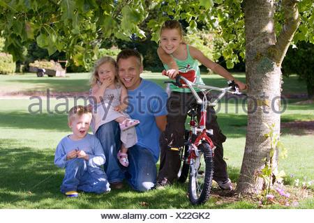 Père de trois enfants 39 à genoux sur l'herbe à côté de tree in garden girl sitting on bike smiling portrait vue avant Banque D'Images
