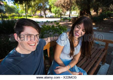 Young couple laughing on park bench Banque D'Images