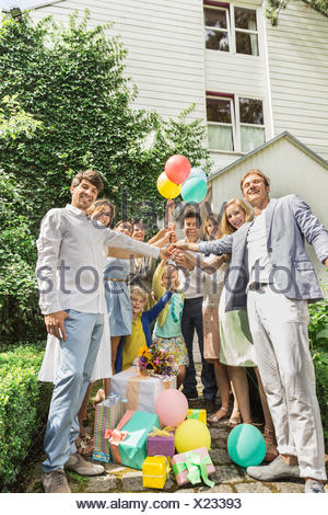 Portrait of three generation family holding up anniversaire ballons dans jardin Banque D'Images