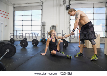 Man helping woman up at gym Banque D'Images