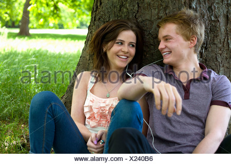 Teenage couple sitting in park Banque D'Images