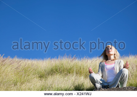 Young woman in yoga position on grassy hill Banque D'Images