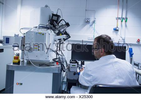 Assistant de laboratoire travaillant avec microscope électronique Banque D'Images