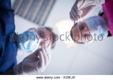 Dentiste et l'assistant se penche au patient avec des outils Banque D'Images