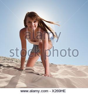 Jolie femme agenouillée dans le sable Banque D'Images