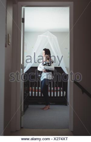 Mère portant son bébé dans la chambre à la maison Banque D'Images