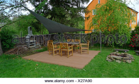 Table de jardin couvert avec de nombreuses chaises en un jardin d'ornement Banque D'Images