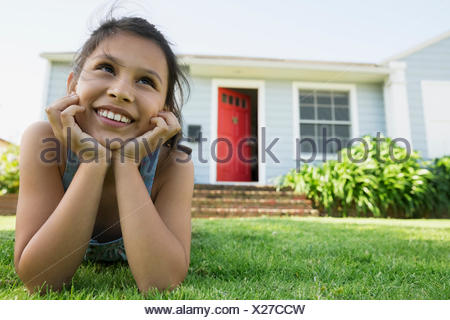 Smiling girl laying in grass dans la cour avant Banque D'Images