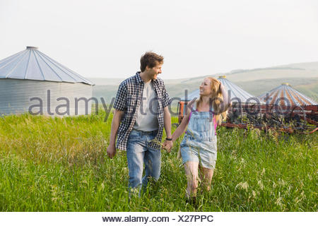 Couple holding hands and walking in rural field Banque D'Images