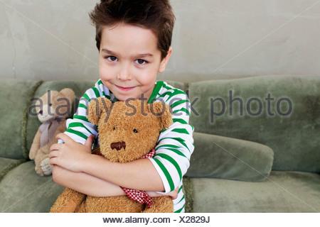 Portrait de jeune garçon sur canapé hugging teddy Banque D'Images