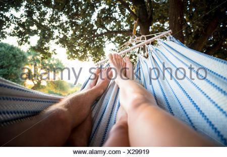 Couple se détendant dans un hamac sous l'arbre Banque D'Images
