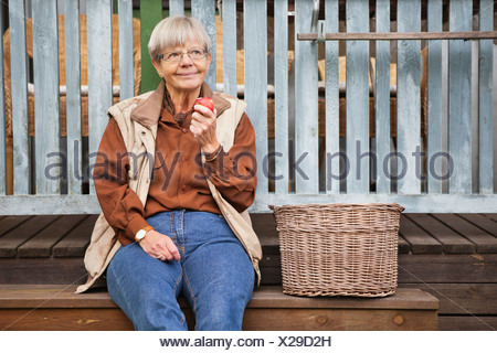 Femme assise avec Apple dans la main Banque D'Images