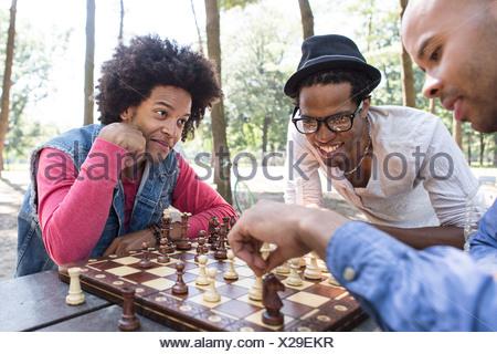 Trois jeunes hommes jouant aux échecs dans le parc