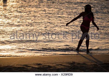 Une jeune femme se promène le long de la surf. Banque D'Images