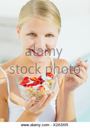 Woman eating muesli avec du yaourt et fraises Banque D'Images