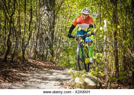 La Suède, Blekinge, Solvesborg, Ryssberget, Mature man riding en vtt à travers la forêt Banque D'Images