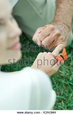 Butterfly Landing sur la main d'une adolescente, l'homme effleurant sa main avec le doigt, sur l'épaule Banque D'Images