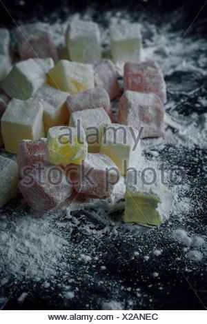 Classic loukoums en deux couleurs saupoudré avec de l'amidon, dont une est mordu. Banque D'Images
