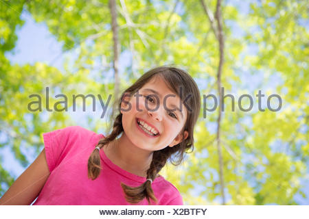 Une jeune fille aux tresses, vêtu d'un haut rose sous un dais d'arbres.