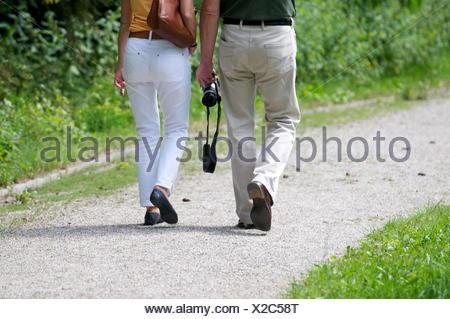 Couple de prendre une marche, l'appareil photo, sac à main, détail, vue arrière, Banque D'Images