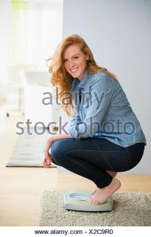 Portrait de femme accroupie sur l'échelle de poids Banque D'Images