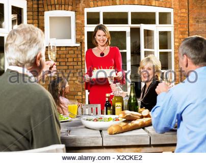 Femme portant le gâteau d'anniversaire à la table Banque D'Images