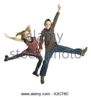 Garçon et fille se tenant la main et sautant Banque D'Images