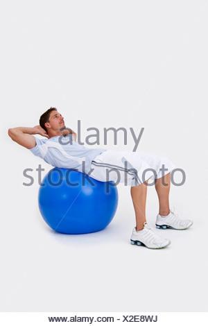Un homme à l'aide d'une boule d'exercice pour faire des sit-ups Banque D'Images
