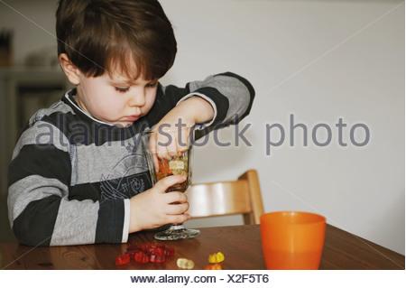 Garçon jouant avec des bonbons à la table Banque D'Images