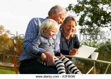 La Suède, Sodermanland, Senior couple sitting with grandson (2-3) à table using digital tablet Banque D'Images