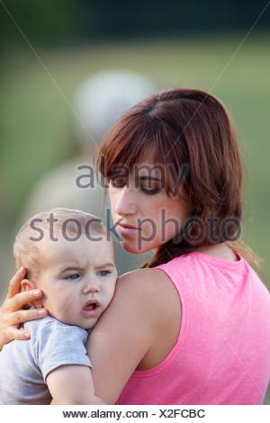 Mère tenant bébé qui pleure à l'extérieur Banque D'Images