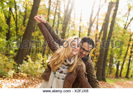 Smiling couple hugging in forest Banque D'Images