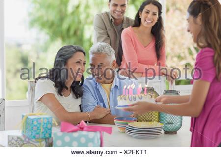 Préadolescent fille présentant le gâteau d'anniversaire aux parents Banque D'Images