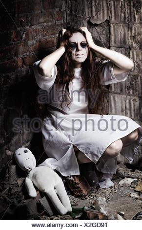 Style horreur shot: crazy étrange jeune fille et sa poupée moppet Banque D'Images