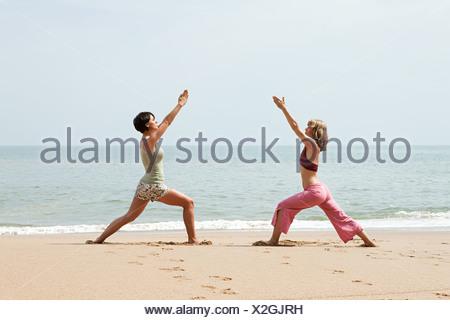 Deux femmes pratiquant le yoga sur une plage Banque D'Images