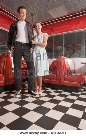 Portrait of young woman standing in diner portant des vêtements de style années 1950