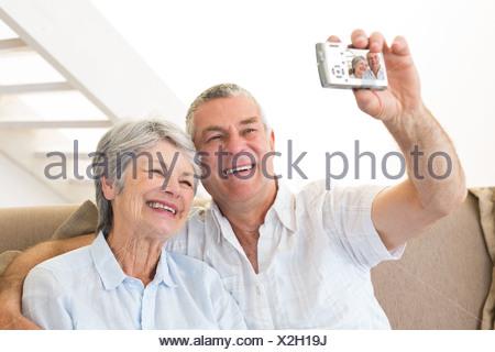 Senior couple sitting on couch selfies prendre une Banque D'Images