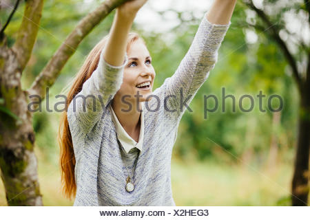 Jeune femme en tenue sur le terrain à tree branch Banque D'Images