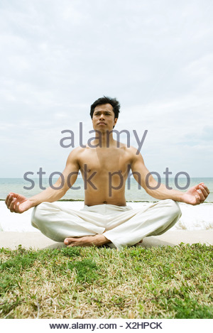Nude man assis en position du lotus, de l'océan en arrière-plan, pleine longueur Banque D'Images