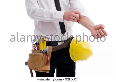 e1b65027d526 ... Jeune homme avec une ceinture d outils et un casque, retrousser ses  manches Banque