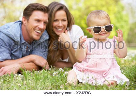Les parents avec bébé fille assise dans le champ de fleurs d'été Banque D'Images