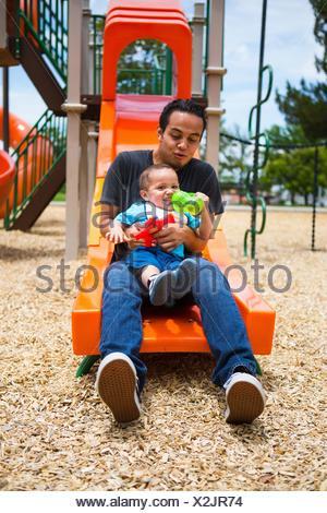 Jeune homme avec tout-petit frère sur l'aire de glisse Banque D'Images