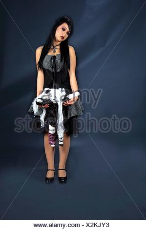 Femme, belle victorienne gothique raven haired girl Vampire gothique dans une robe noire et grise, debout dans l'obscurité avec une poupée Banque D'Images