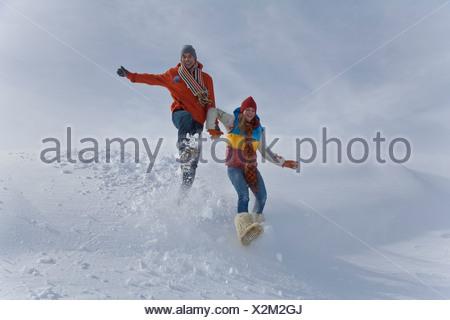Jeune couple qui saute dans la neige sur journée d'hiver Banque D'Images