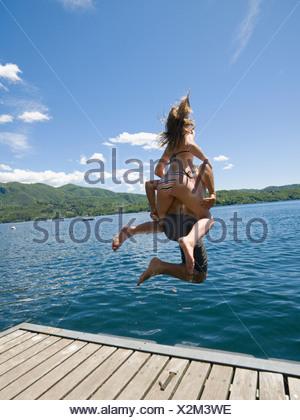 L'Italie, Piémont, vue arrière du père et fille (14-15) de sauter du quai en bois dans le lac d'Orta Banque D'Images