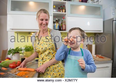 Garçon imbécile autour avec des carottes alors que mère rit Banque D'Images